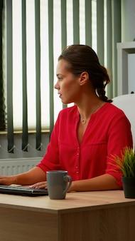 Drukke werknemer typen op computer zittend op een stoel in moderne kantoren. ondernemer die werkt in een modern professioneel kantoor, werkplek in een persoonlijk bedrijf, typt op het toetsenbord van de computer en kijkt naar desktop