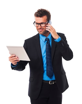 Drukke zakenman die aan tablet en mobiele telefoon werkt