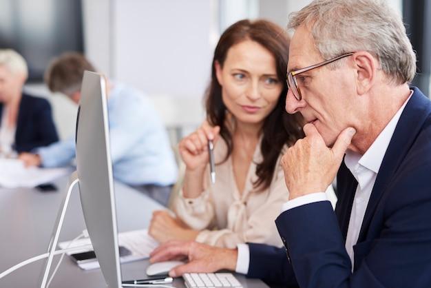 Drukke zakenman die een computer gebruikt tijdens een zakelijke bijeenkomst