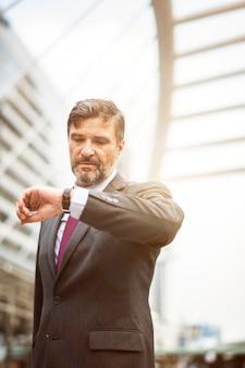 Drukke zakenman die zijn horloge controleert