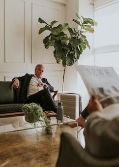 Drukke zakenman met een koffer die naar de tijd kijkt