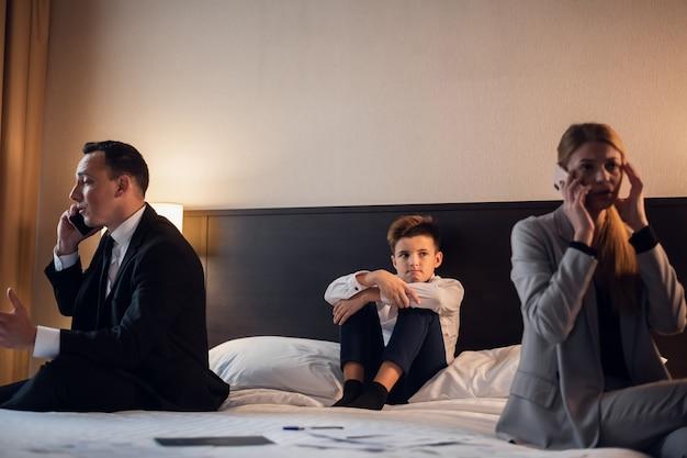 Drukke zakenmensen op zakenreis met hun zoon die verdrietig is door gebrek aan aandacht
