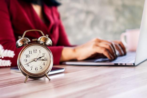 Drukke zakenvrouw die hard aan het werk is met een wekker die laat voor de lunch laat zien