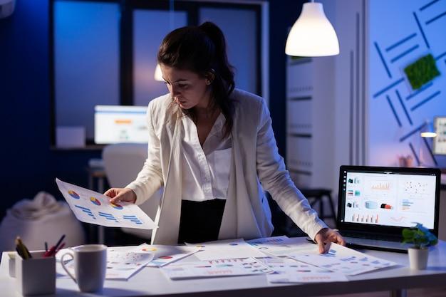 Drukke zakenvrouw die werkt aan financiële rapporten die nummers controleert voor uitvoerende vergadering