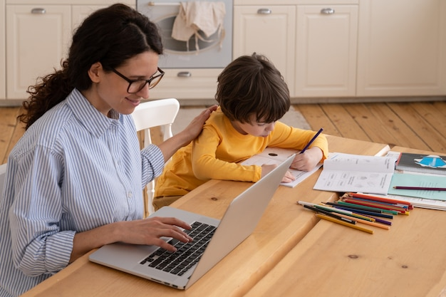 Drukke zakenvrouw werkt vanuit huis naast zijn zoon
