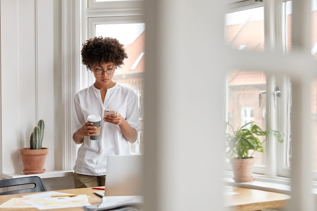 Drukke zwarte succesvolle zakenvrouw of ondernemer controleert melding op mobiele telefoon, drinkt afhaalkoffie