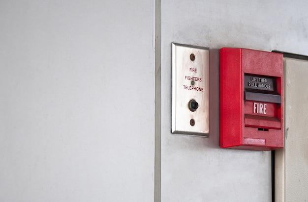 Drukknopschakelaar brandalarm op grijze muur voor alarm en beveiligingssysteem met brandblusser