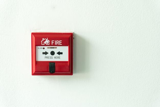 Drukknopschakelaar brandalarmkast op cementmuur voor waarschuwing en beveiligingssysteem.