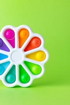 Drukt met een vinger antistress speelgoed pop het op groene achtergrond kleurrijke siliconen poppit speelgoedbel ...