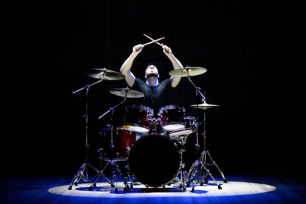 Drummer die de trommels op het stadium speelt