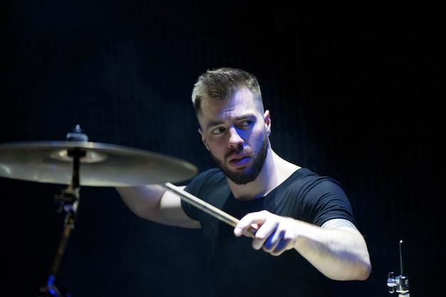 Drummer in een dop en koptelefoon speelt drums tijdens een concert