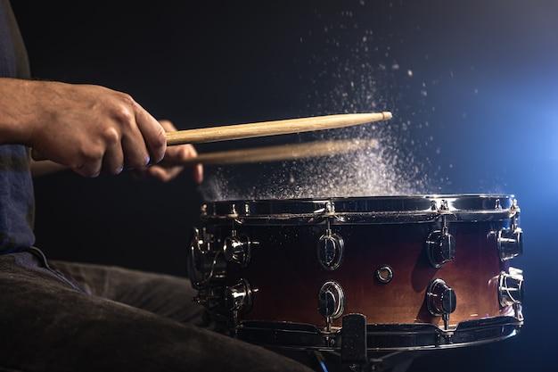 Drummer met drumstokken die snare drum raken met opspattend water op zwarte achtergrond onder studioverlichting close-up.