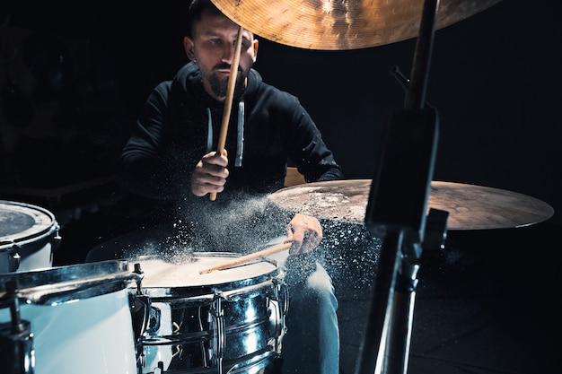 Drummer repeteert op drums voor rockconcert. man die muziek opneemt op drumstel in studio met showeffect in de vorm van meel