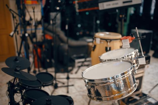 Drumstel op showcase in muziekwinkel, close-up weergave, niemand. assortiment in muziekinstrumentenwinkel, professionele apparatuur voor muzikanten en uitvoerders