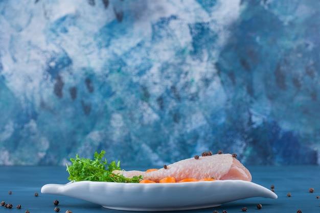 Drumstick en wortelen op een schotel, op de blauwe achtergrond.