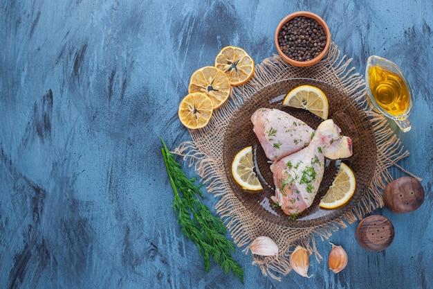 Drumsticks en citroen op een glazen plaat naast gedroogde citroen, kruidenkom, dille en olie op een jute servet, op de blauwe achtergrond.