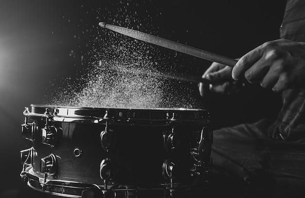Drumstokken raken snaredrum met opspattend water op zwarte achtergrond onder podiumverlichting.