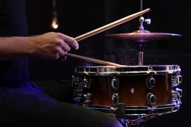 Drumstokken raken snaredrum met opspattend water op zwarte achtergrond onder studioverlichting close-up.