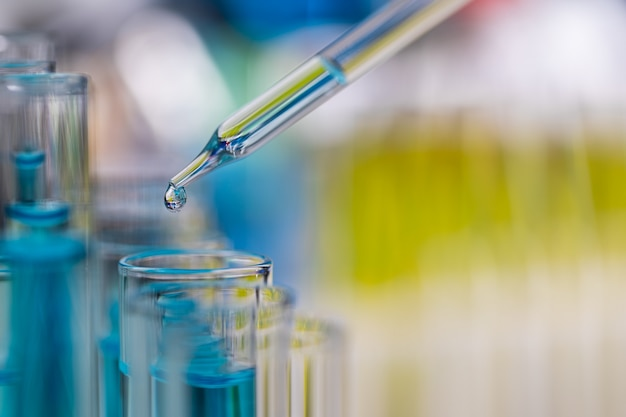 Druppel blauwe vloeistof van droper die naar de reageerbuis in het laboratorium valt met een heldere kleurvervagingsachtergrond.