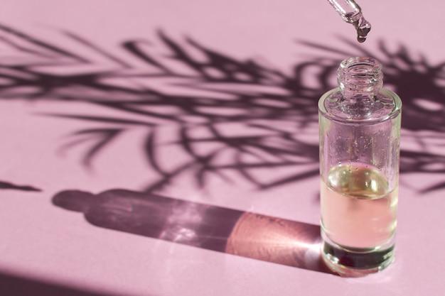 Druppel valt uit een pipet in een glazen fles met cosmetische olie of serum
