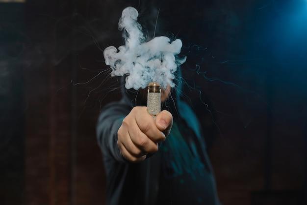 Druppelaar in één hand die een wolk van rook maakt