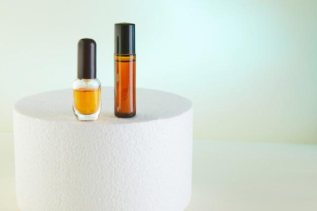Druppelflesje - amber glas parfum, douchegel, flessen zonder label op wit podium.