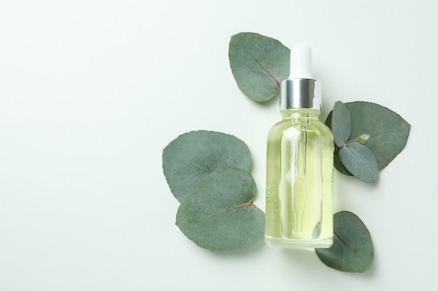 Druppelflesje eucalyptusolie en bladeren op witte achtergrond