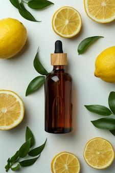 Druppelflesje met olie, citroenen en bladeren op witte geïsoleerde achtergrond