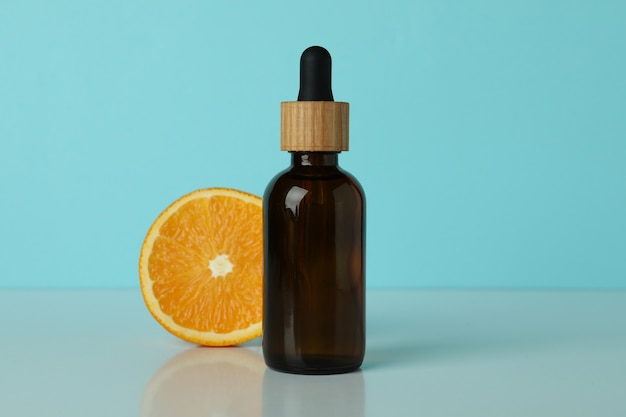 Druppelflesje met olie en sinaasappel tegen blauwe geïsoleerde achtergrond