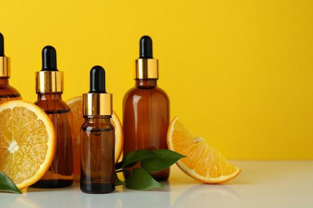 Druppelflessen met olie en sinaasappelen tegen gele achtergrond
