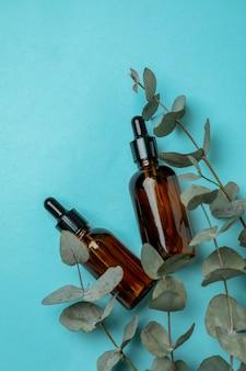 Druppelflessen olie en eucalyptustakjes op blauwe achtergrond