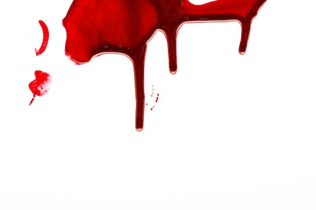 Druppels bloed lopen naar beneden. bloed stroomt langs de witte muur