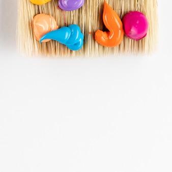 Druppels kleurrijke verf op penseel