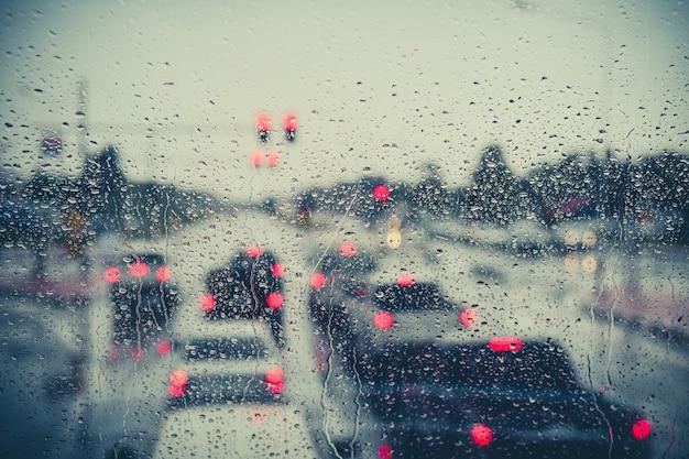 Druppels regen op blauw glas met straat bokeh lichten.