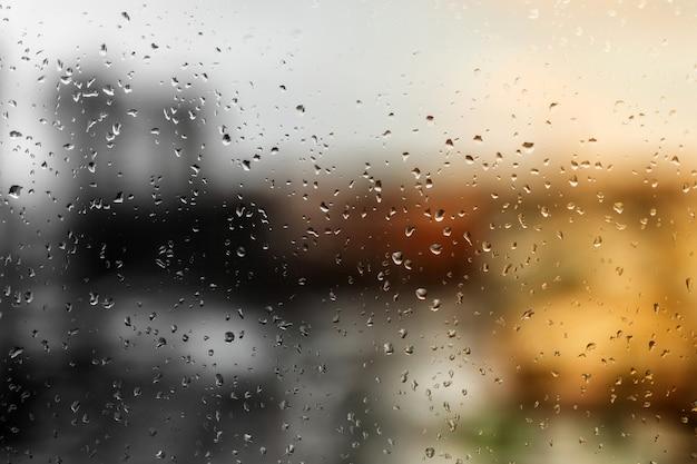 Druppels regen op een vensterruit, straatgebouwen op de achtergrond.