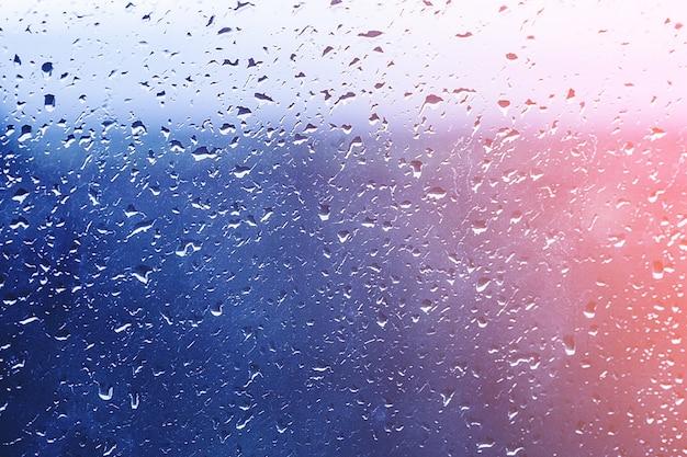 Druppels regen op het raam. water op het glas. lopende druppels. conceptuele achtergrond.