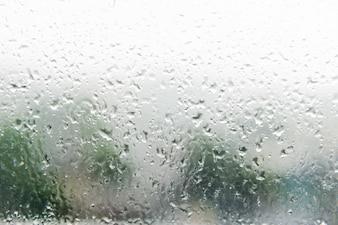 Druppels regen op het schuine venster (glas)