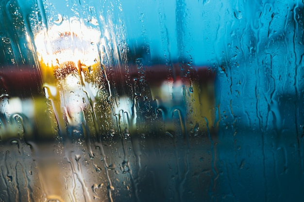 Druppels regen op venster met abstracte bokehlichten.