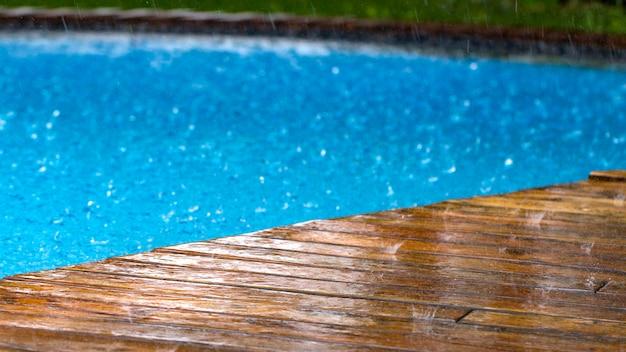 Druppels regen vallen op een houten terras en een brug bij het zwembad van dichtbij