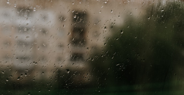 Druppels regenwater op het glas. druppels verzameld op het raam tegen de achtergrond van gebouwen met meerdere verdiepingen.