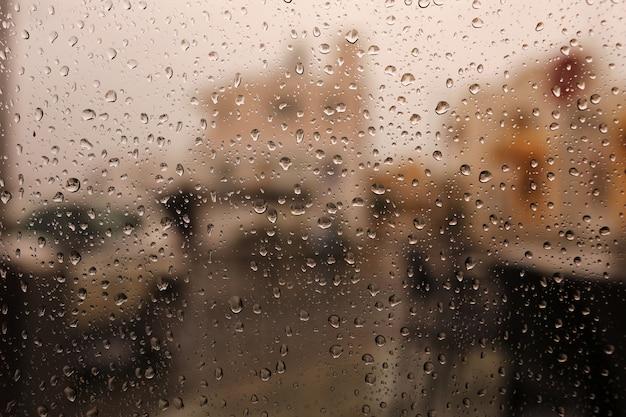 Druppels water uit de regen stromen door het glas. regendruppels op raam. verdriet, verlangen, saaiheid, herfstdepressie, somberheid. neerslag, druppelen, regenen, waterdruppels.
