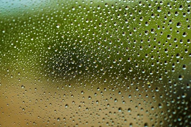 Druppels water voor de achtergrond op vensterglas om ontwerp en aardachtergrond samen te vatten. venster na een zomerregen met een groene tuinachtergrond druppels regen op het venster, regenachtige dag, donkere toon.