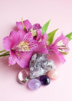 Druse amethist in de vorm van een hart, bergkristal, rozenkwarts en alstroemeria bloemen op een roze ondergrond