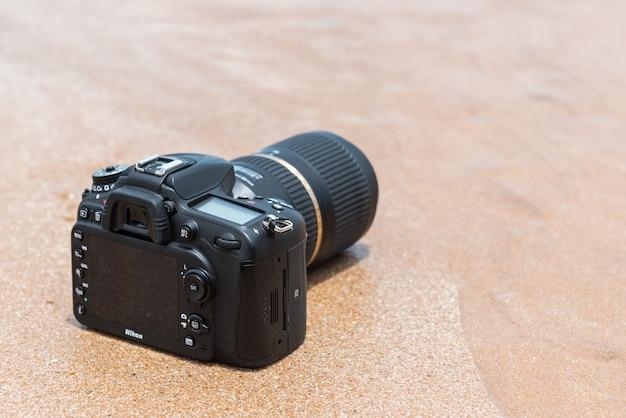 Dslr-camera op strand nat van water overzeese golf