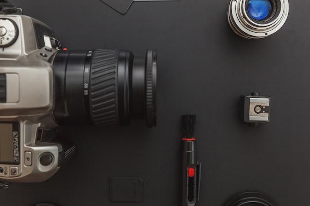 Dslr-camerasysteem, camera-reinigingsset, lens en camera-accessoire op zwarte tafel