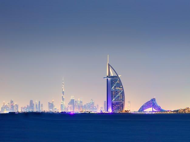 Dubai - 17 november 2017: skyline van dubai 's nachts met burj al arab op voorgrond verenigde arabische