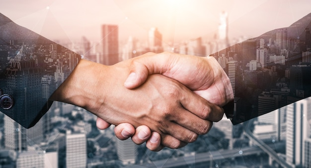 Dubbel blootstellingsbeeld van bedrijfsmensenhanddruk op stadskantoorgebouw in het tonen van vennootschap