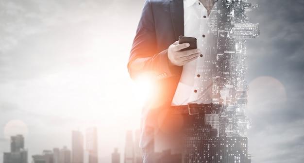 Dubbel blootstellingsbeeld van business communication network technology concept - mensen uit het bedrijfsleven met behulp van smartphone of mobiele telefoon op moderne stadsgezicht achtergrond