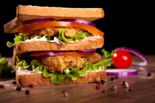 Dubbel broodje, met kip, sla, tomaat, ui, peper en saus, op een houten tafel en zwarte achtergrond.