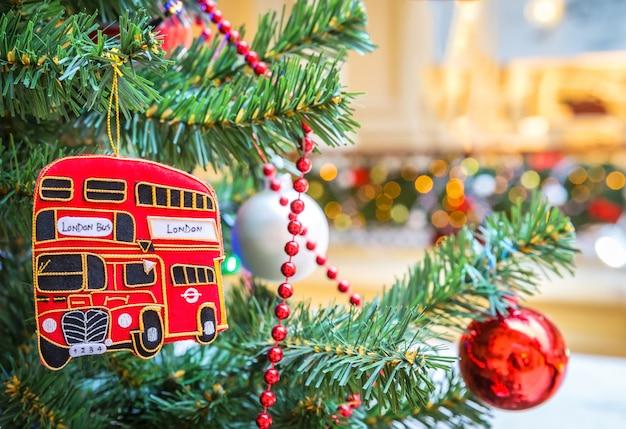 Dubbeldekker bus speelgoed en kerstmis bal in kerstboom